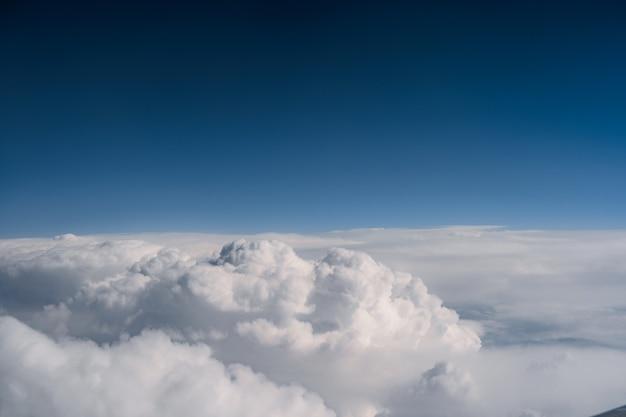 Nuvens brancas contra uma vista do céu azul escuro da janela do avião