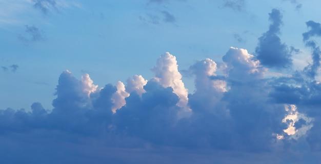 Nuvens brancas e escuras iluminadas pelo sol no céu azul