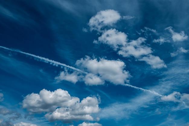 Nuvens brancas e neblina contra a trilha de condensação do céu azul de um avião voando em alta altitude trilha de vapor de água e cristais de gelo