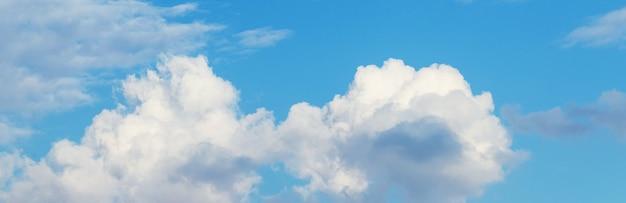 Nuvens brancas encaracoladas em um céu azul com tempo ensolarado, panorama