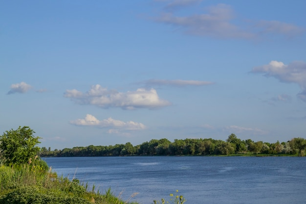Nuvens brancas macias no céu azul em um dia de verão ensolarado sobre o rio.