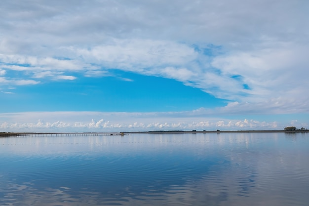 Nuvens brancas refletidas em um lago.