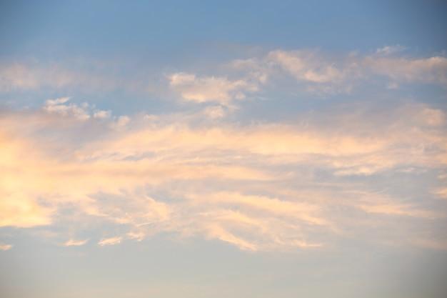 Nuvens cirrus brancas e rosa em um céu azul em uma noite de verão