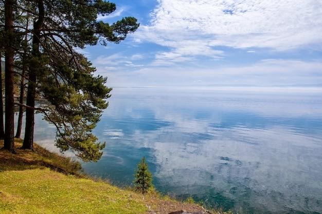 Nuvens com reflexo na água com pinheiros, lago baikal