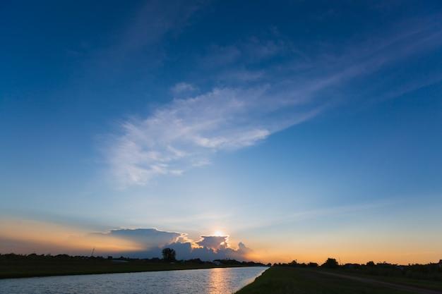 Nuvens com reflexo no rio ao pôr do sol ou nascer do sol