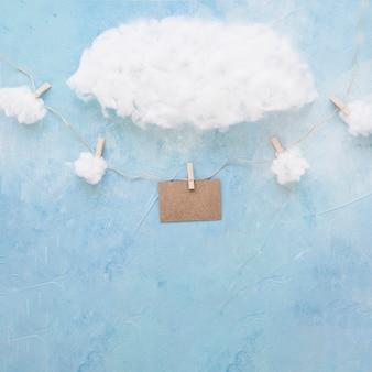 Nuvens de algodão sobre o cartão marrom decorativo pendurar com prendedores de roupa