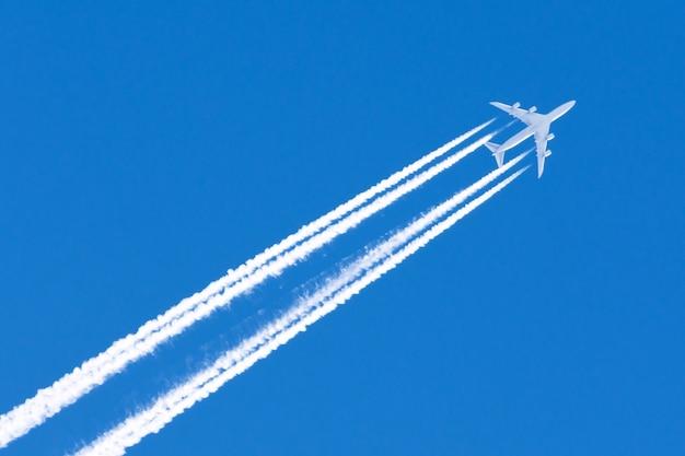 Nuvens de contrail do aeroporto da aviação do avião quatro grandes motores.