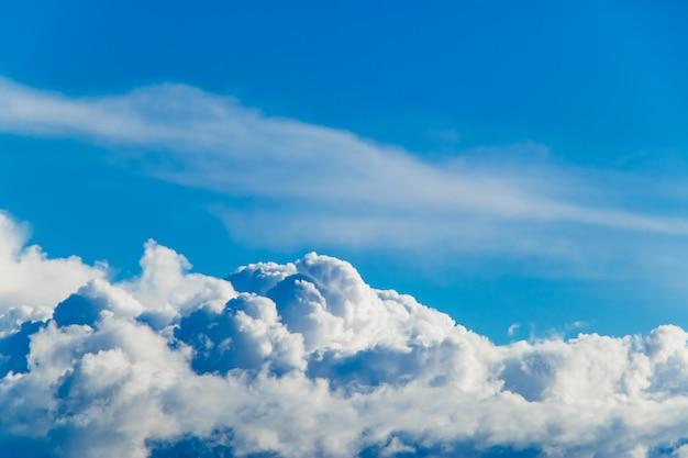 Nuvens de cúmulo macias brancas contra um céu azul.