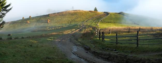 Nuvens de neblina ao amanhecer no topo da colina e roud sujo (montanhas dos cárpatos, ucrânia). seis tiros costuram a imagem.
