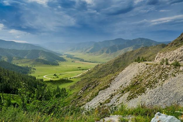 Nuvens de tempestade em uma passagem na montanha. vista da passagem da montanha para a estrada sinuosa que passa abaixo. perigosa estrada de montanha sinuosa. altai
