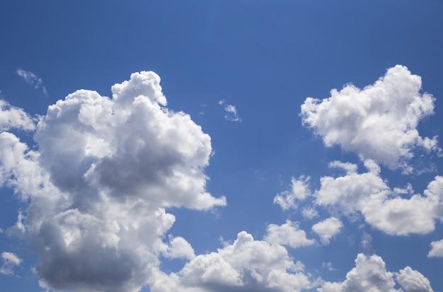 Nuvens de textura em forma de branco estão no céu azul puro com a luz do sol como pano de fundo.