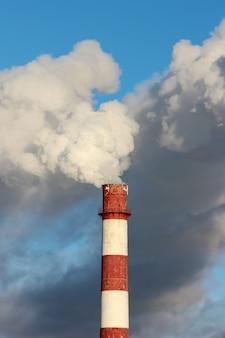 Nuvens densas do fumo ou vapor fora da tubulação no fundo do céu azul.