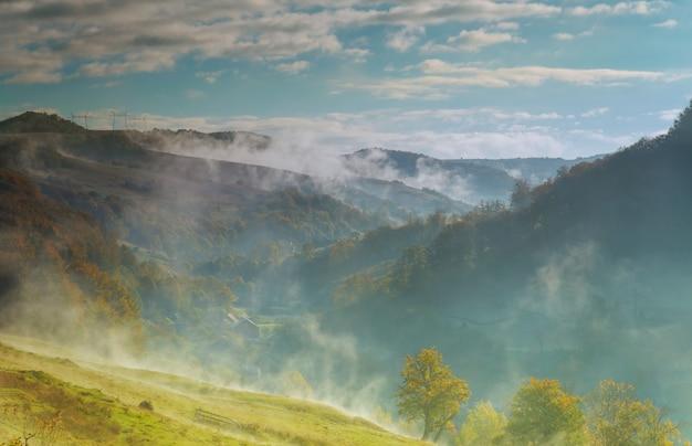 Nuvens dramáticas com montanha e árvore nevoeiro de outono