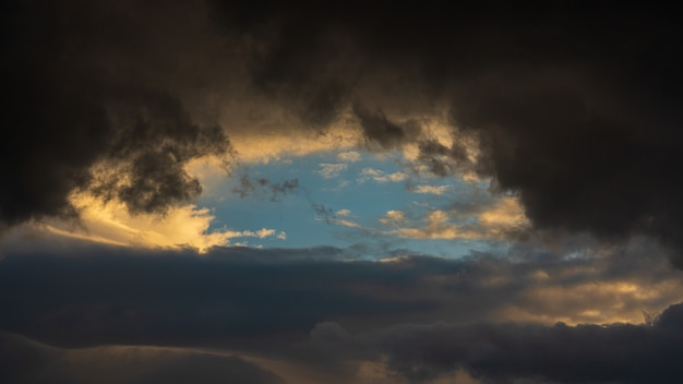 Nuvens dramáticas iluminadas ao nascer do sol flutuando no céu fundo de meteorologia de clima natural