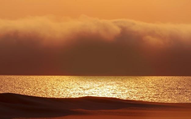 Nuvens dramáticas pesadas e céu claro sobre o oceano atlântico. belo pôr do sol no deserto africano