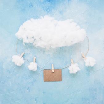 Nuvens e cartão pendurado na corda com prendedores de roupa em fundo azul