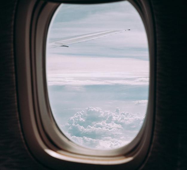 Nuvens e céu pela janela de uma aeronave.