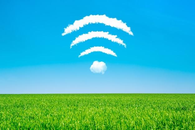 Nuvens em forma de símbolo de wifi em um céu azul e um prado verde