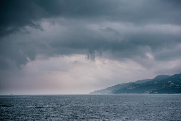Nuvens escuras e chuvosas sobre a superfície do mar e a paisagem das montanhas