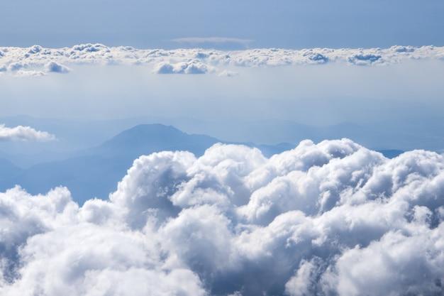 Nuvens fofas sobre a vista das montanhas da janela do avião