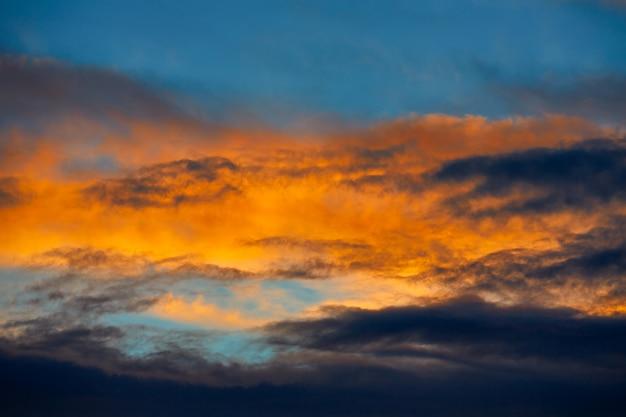 Nuvens laranja do sol em um céu azul
