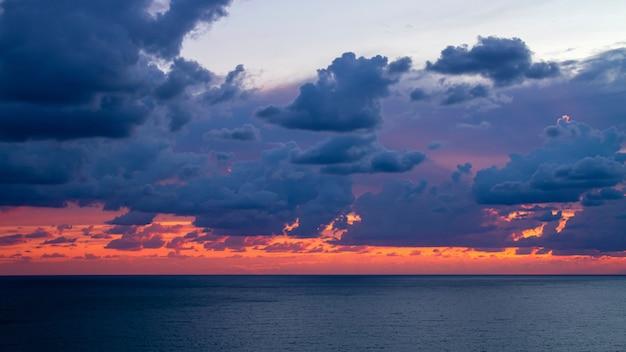 Nuvens laranja e roxas sobre o mar azul ao pôr do sol