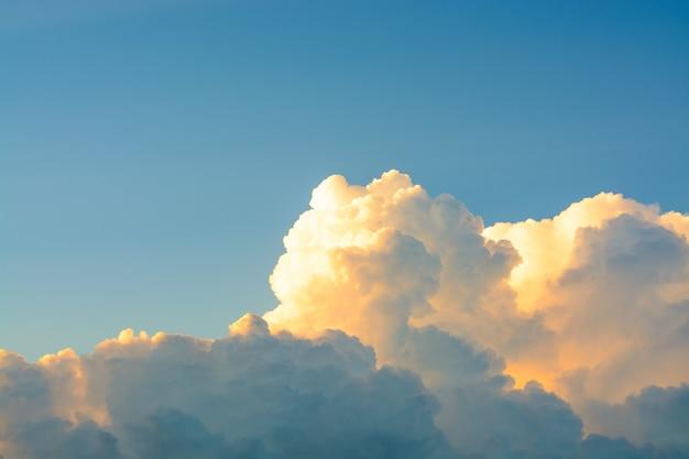 Nuvens macias brancas no céu azul claro em um por do sol alaranjado brilhante