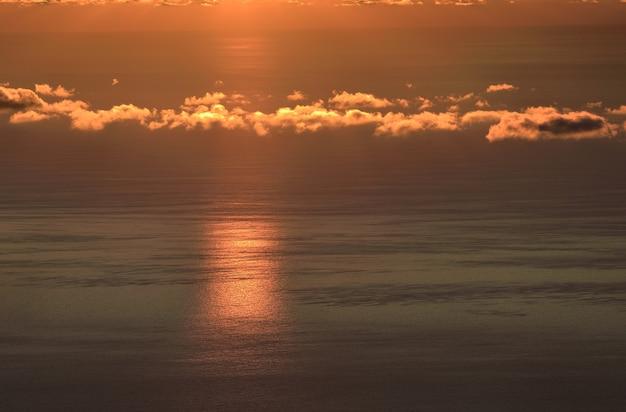 Nuvens na luz dourada do sol nascente no fundo da superfície do mar