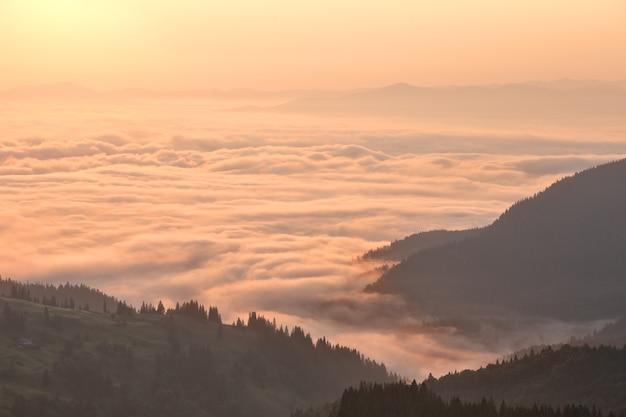 Nuvens nas montanhas ao nascer do sol