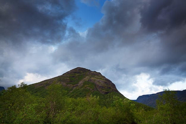 Nuvens no céu acima das montanhas iluminadas pelo sol ao pôr do sol.