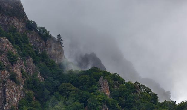 Nuvens no topo das montanhas rochosas cobertas de árvores. fotografado no cáucaso, na rússia.