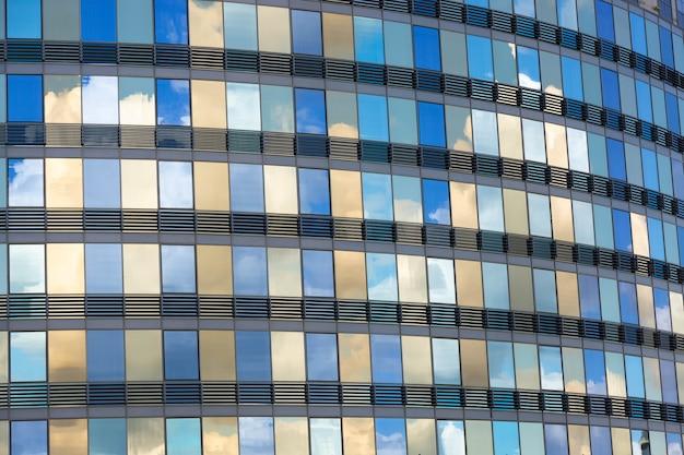 Nuvens refletidas nas janelas de um prédio comercial moderno