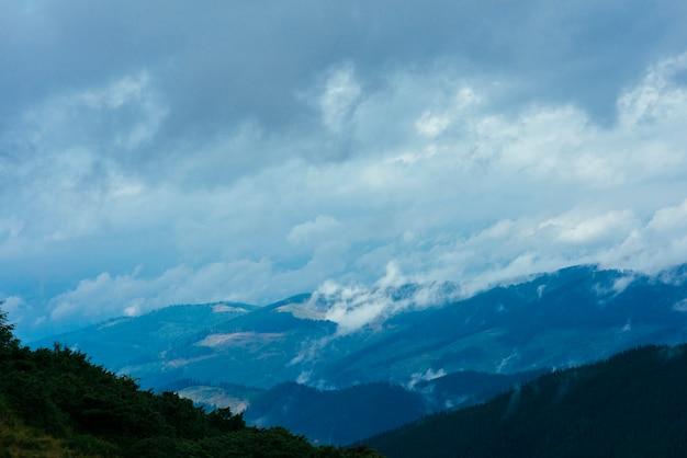 Nuvens sobre a montanha coberta de árvores verdes