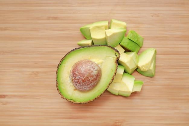 O abacate cortou a metade e desbastou no fundo da placa de madeira.