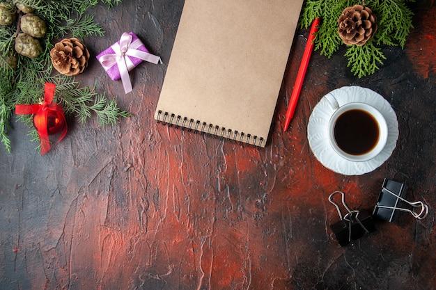 O abeto ramifica uma xícara de acessórios de decoração de chá preto e um presente ao lado do caderno com uma caneta em fundo escuro