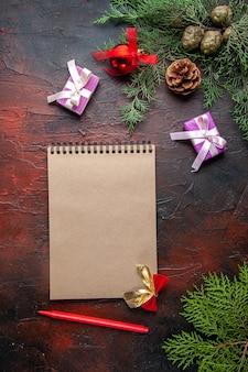 O abeto ramifica uma xícara de acessórios de decoração de chá preto e um presente ao lado do caderno com uma caneta na visão vertical de fundo escuro