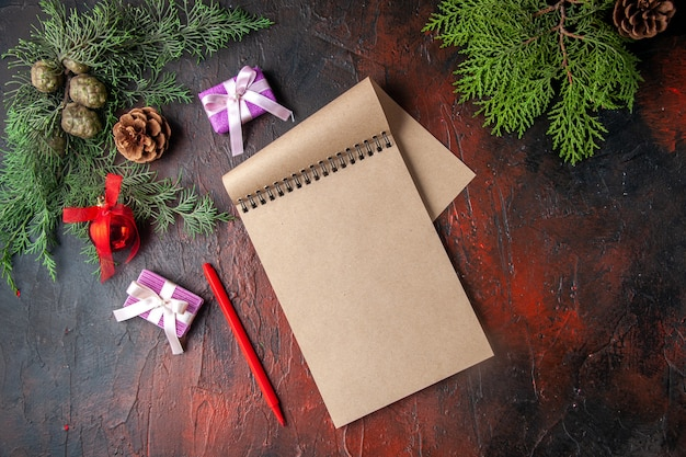 O abeto ramifica uma xícara de acessórios de decoração de chá preto e um presente ao lado do caderno com uma caneta na visualização horizontal de fundo escuro