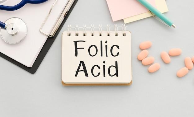 O ácido fólico é escrito em um caderno em um fundo azul ao lado de comprimidos, máscara e caneta.