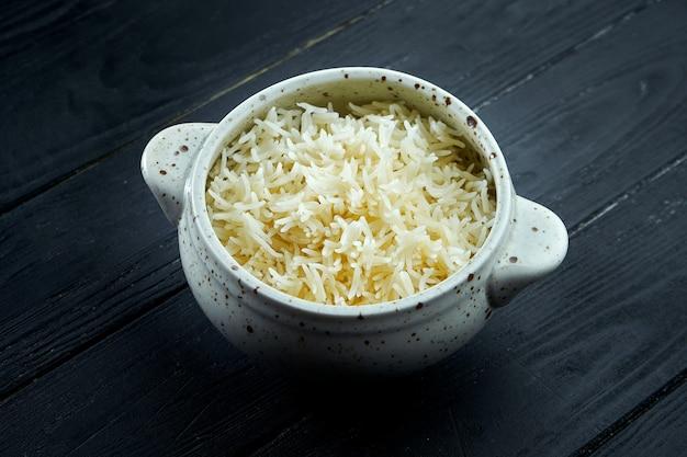 O acompanhamento clássico é o arroz com açafrão em uma tigela branca. dieta e comida vegetariana. fundo de madeira escura