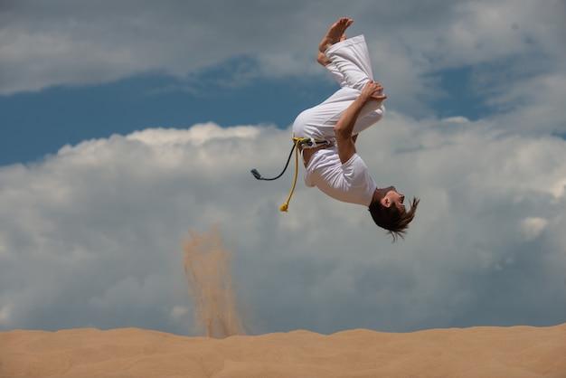 O acrobat executa um truque acrobático, cambalhota na praia.