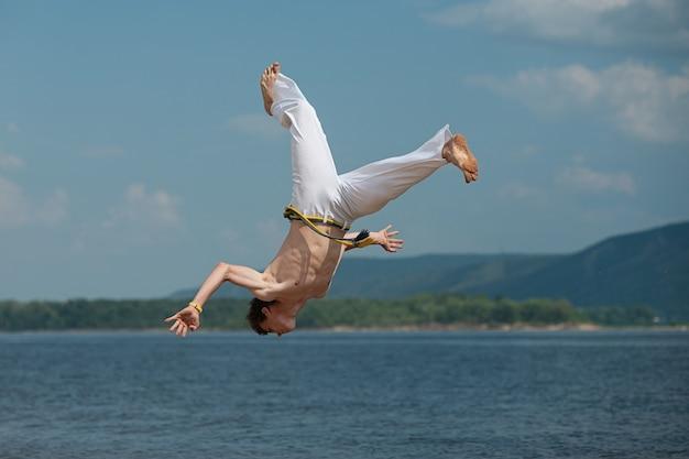 O acrobat faz um truque acrobático, dando cambalhotas na praia.