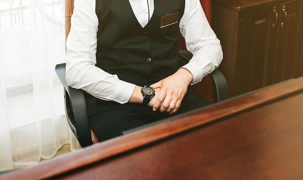 O administrador está sentado na recepção do hotel. foto de negócios do empregado homem. recepcionista de cara jovem de uniforme preto está trabalhando.