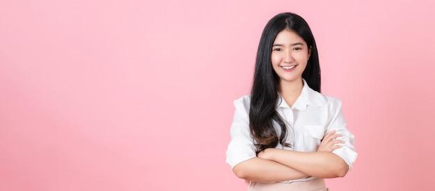 O adolescente asiático de sorriso está e braços cruzados no rosa.