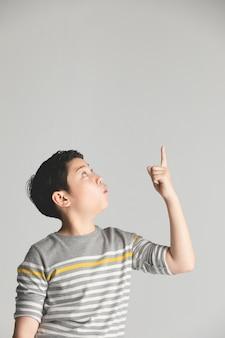 O adolescente asiático do preteen aponta acima sobre o fundo cinzento.