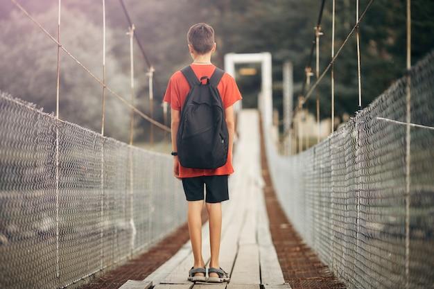 O adolescente com uma trouxa nas montanhas, um menino cruza um rio da montanha em uma ponte de suspensão.