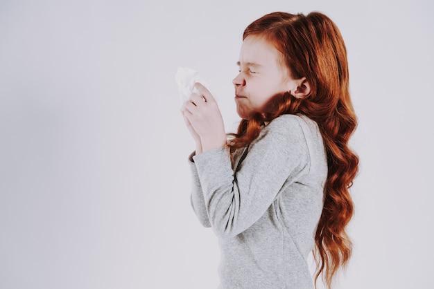 O adolescente de cabelo vermelho sneezes, no fundo cinzento.