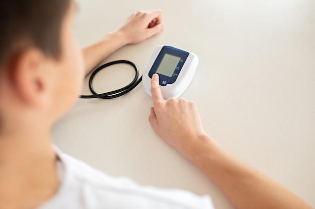O adolescente está medindo a pressão sanguínea com o monitor na casa.