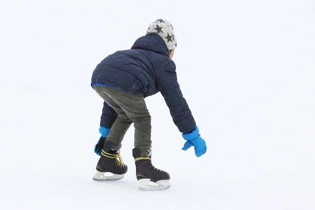 O adolescente está patinando na pista de gelo
