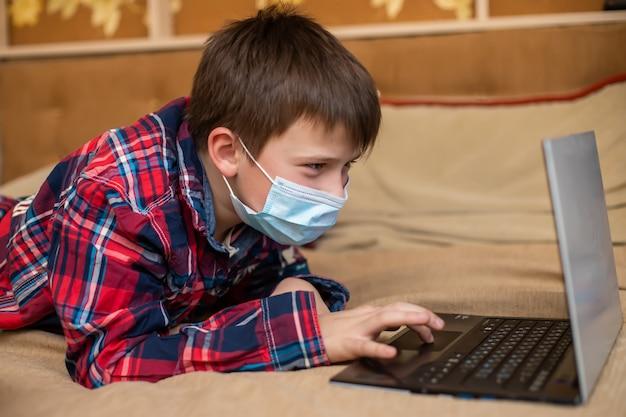 O adolescente na máscara médica protetora tosse no punho. auto-educação remota distante.