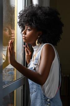 O adolescente olha pela janela com o vidro encharcado de chuva deprimido em meio à pandemia de covid 19